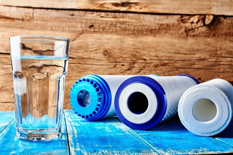 Carbon cartridges and a glass of water on a wooden background_ivan_kislitsin_shutterstock