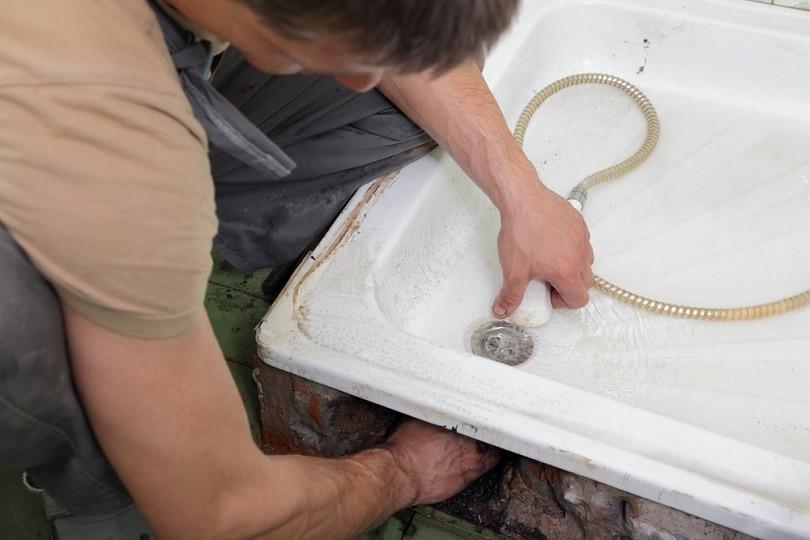 Plumber checking drain_sima_shutterstock