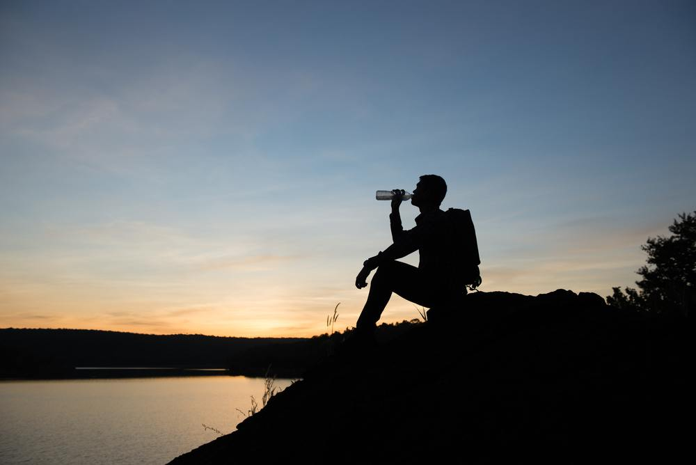 man drinking water hiking